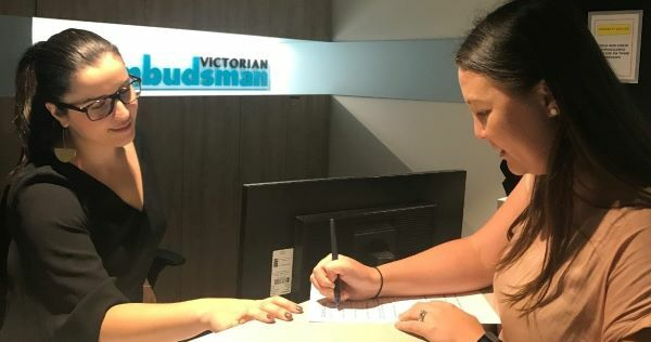 A woman is visiting the Ombudsman office. She is writing something down. A staff member is nearby, ready to assist.