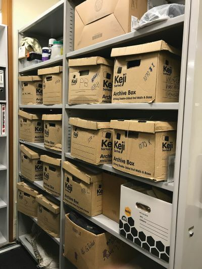 About 14 archive boxes placed across four shelves