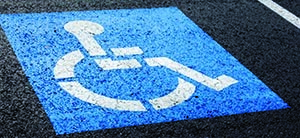 International Symbol of Access (ISA) painted in blue and white on the bitumen inside a car parking space.
