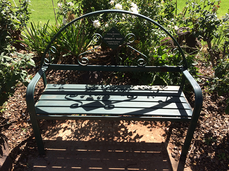A green powder-coated metal bench chair. A person's name is on a plaque in the middle, with the words